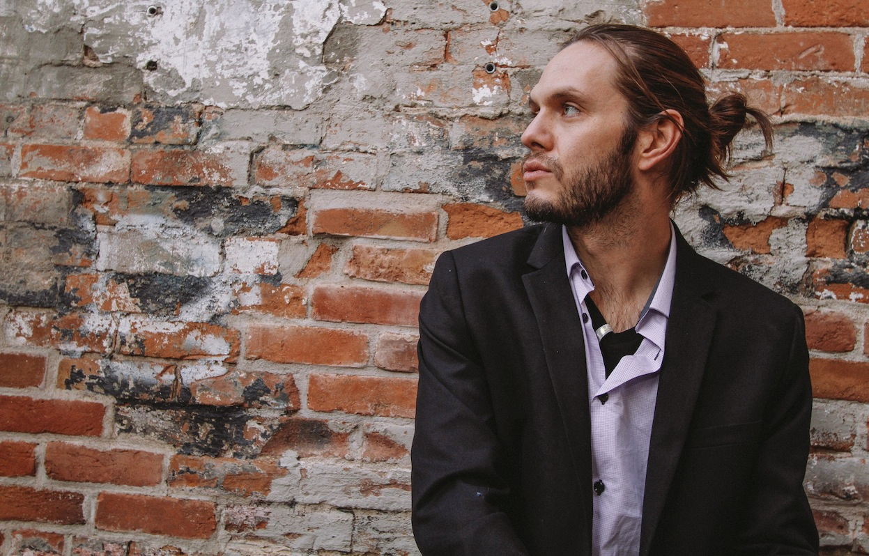 Man in suit jacket and hair in a ponytail faces his right in front of a brick wall