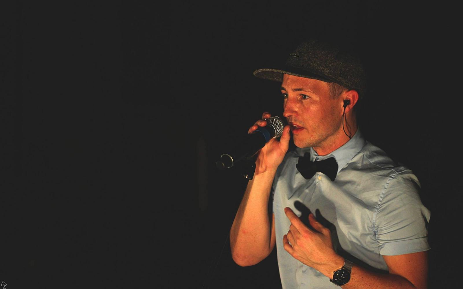 Man in baseball cap beatboxes into microphone. Dark background
